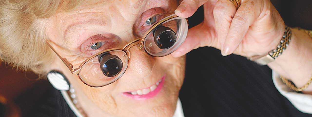older woman with biopic glasses smiling
